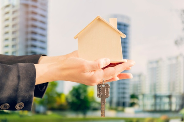 close-up-female-s-hand-holding-wooden-house-model-keys-against-blurred-building-backdrop_23-2148038696